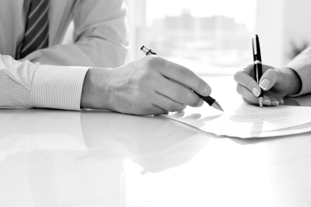 dos personas firmando documentos